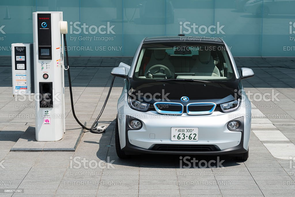 Electric car being charged at charging station stock photo