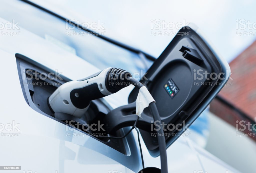 Electric car being charged. Low angle view. stock photo
