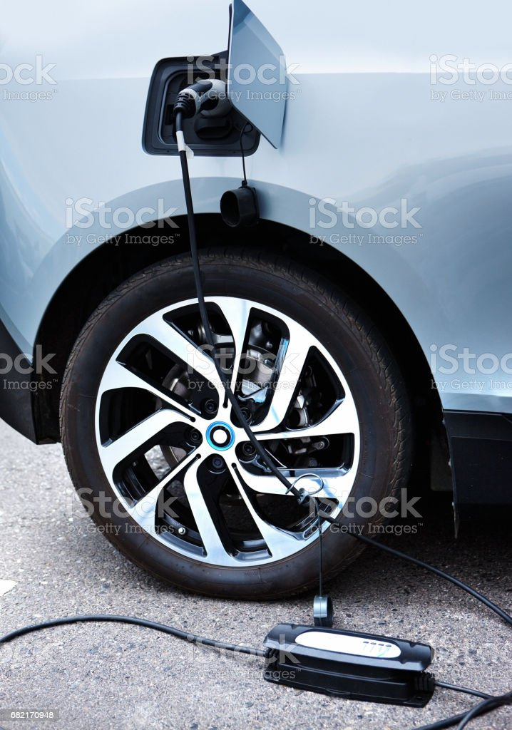 Electric car being charged.  Vertical. stock photo