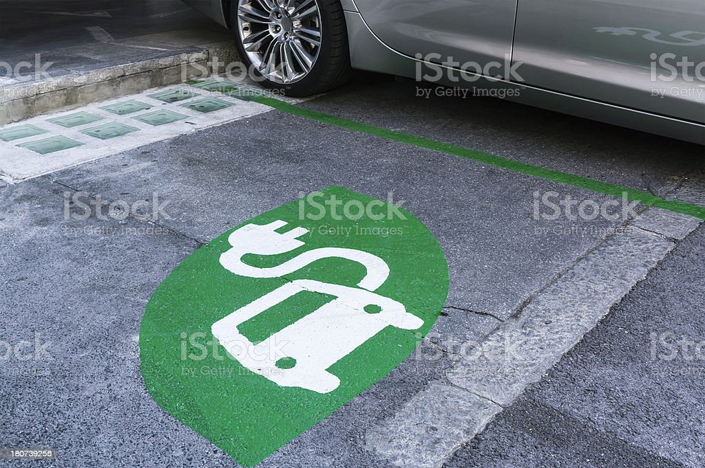 Electric car, charging station, green sign and parking place royalty-free stock photo