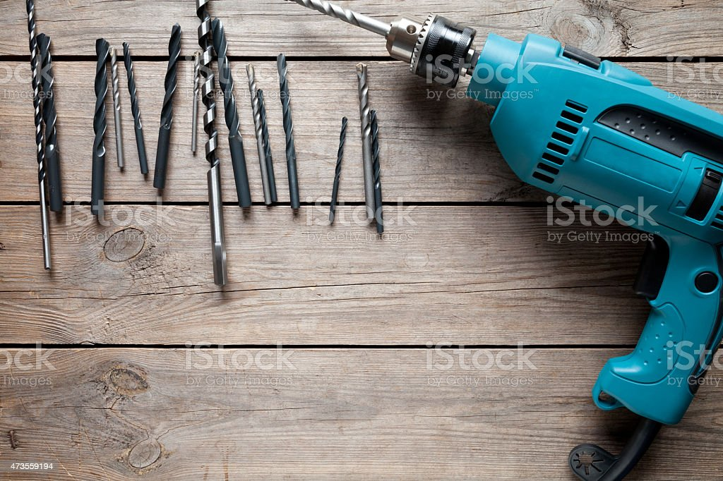 Electric drill on old wooden table stock photo