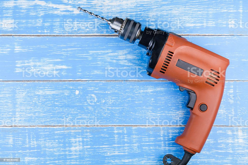 Electric drill with a drill on blue wooden table background stock photo