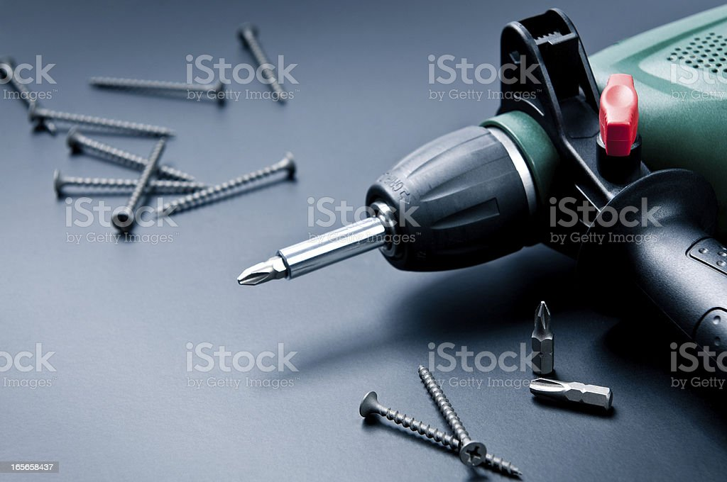Electric drill with screws and screwdrivers on dark background stock photo