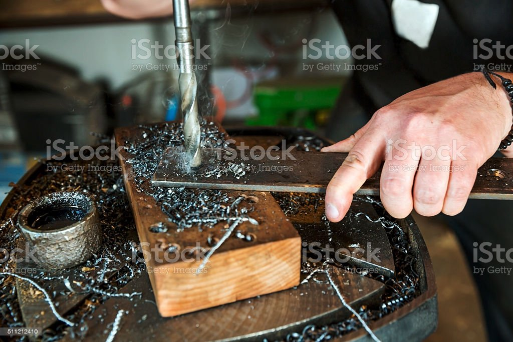 Electric drilling machine in processing a metallic part stock photo