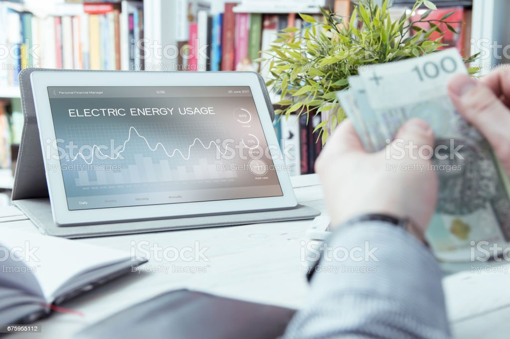 Electric energy usage application made in graphic program and man holding money stock photo