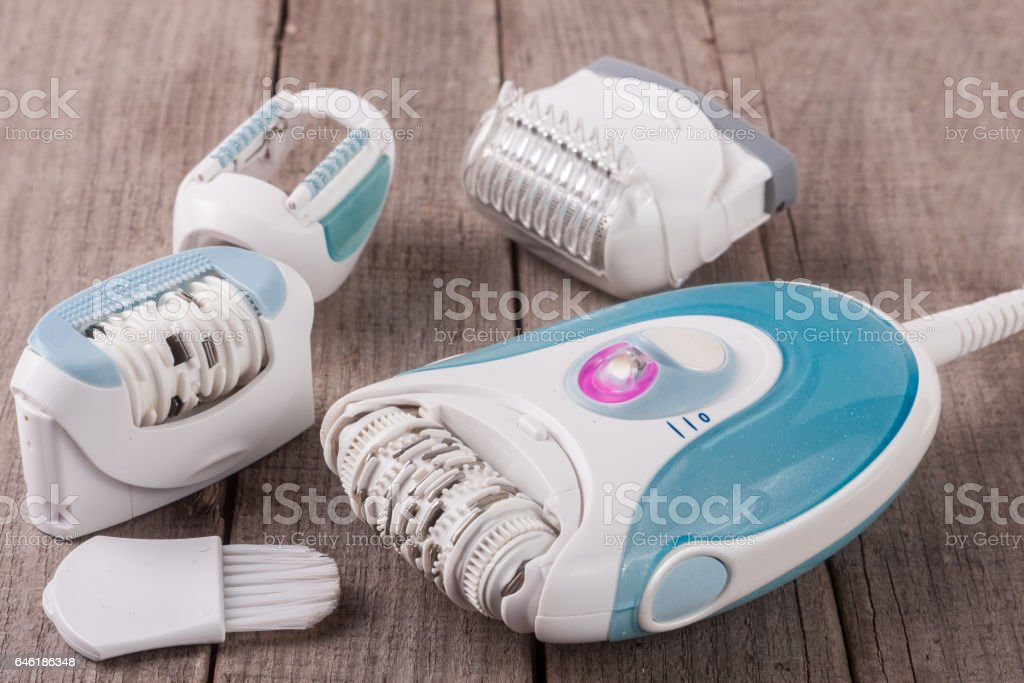 electric epilator hair on an old wooden background stock photo