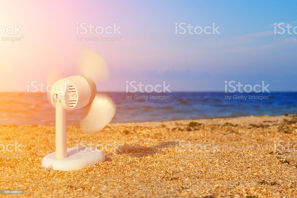 electric fan blowing on the beach in hot summer stock photo