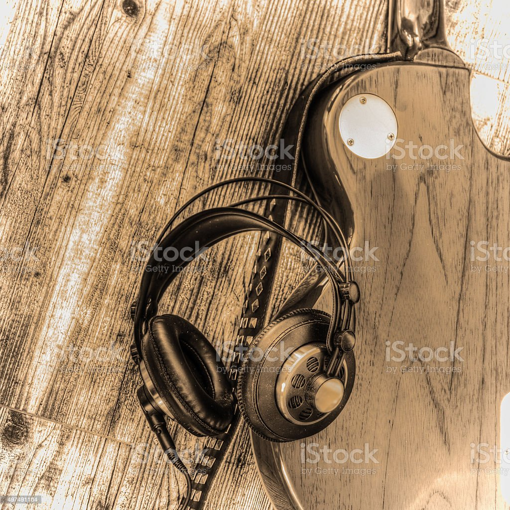 electric guitar and headphones in sepia tone stock photo