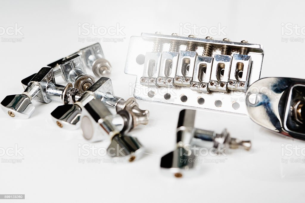 Electric guitar bridge, tuners and jack plate on white stock photo