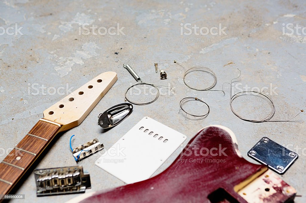 Electric guitar dismantled and in separate parts on grungy flooor stock photo