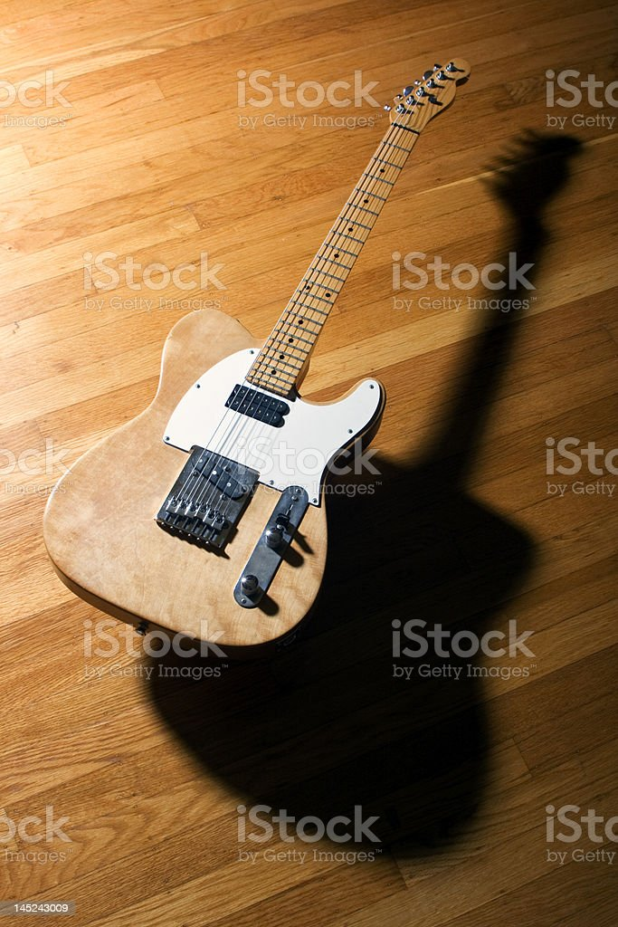 Electric Guitar floating on a wood floor stock photo