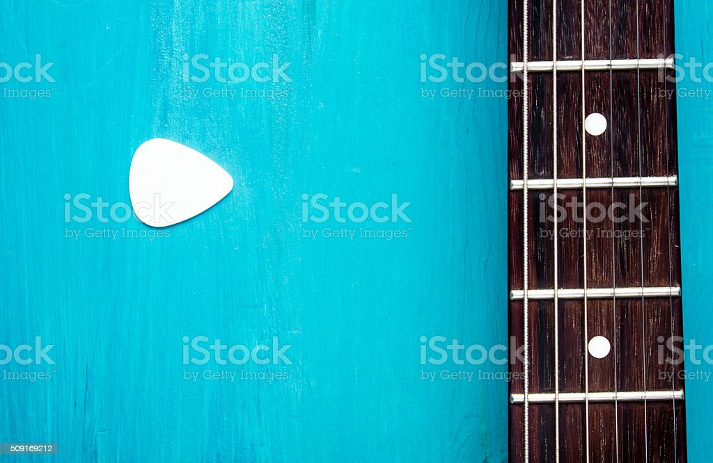 Electric guitar fretboard with colored picks on  wooden background stock photo
