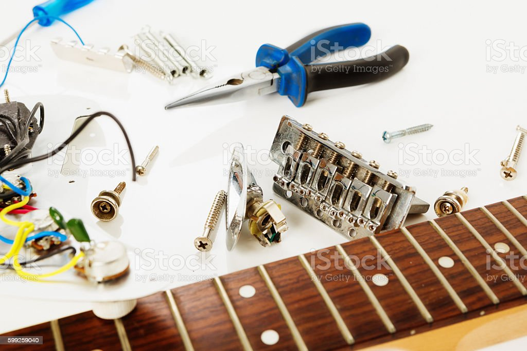 Electric guitar in pieces on workbench awaits re-assembly stock photo