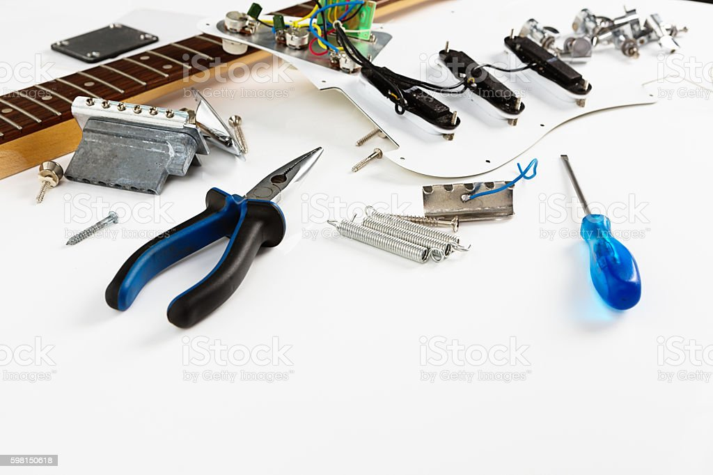 Electric guitar parts on workbench with tools stock photo