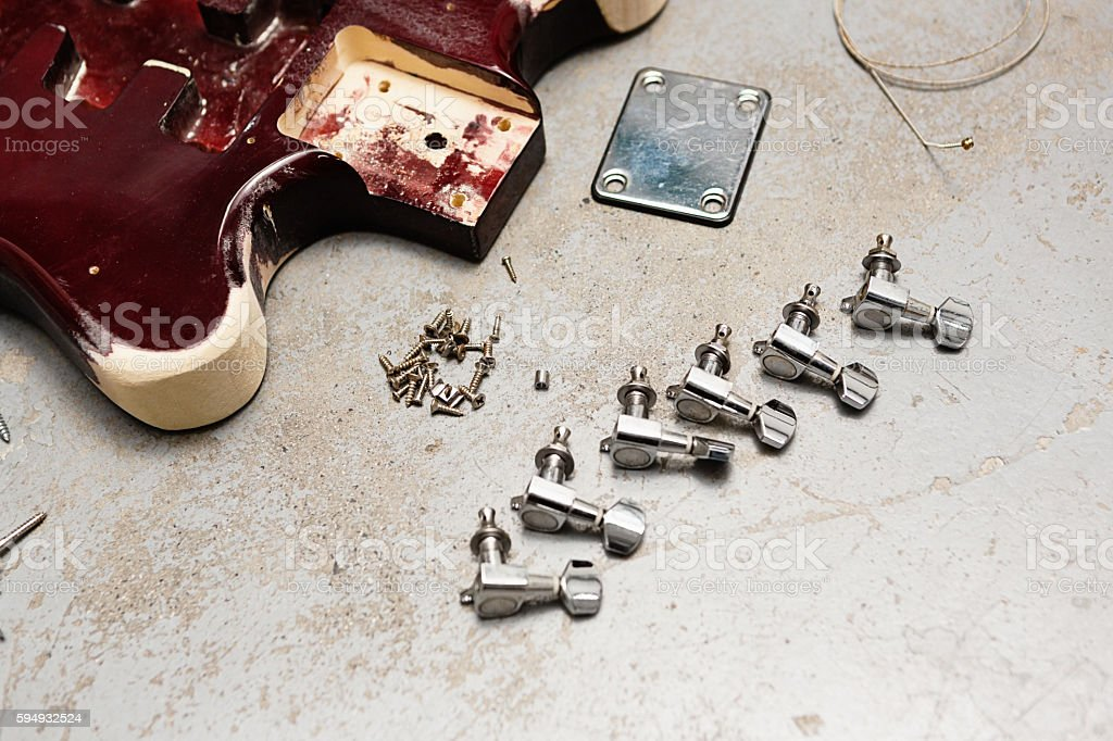 Electric guitar taken apart with pieces lying on floor stock photo