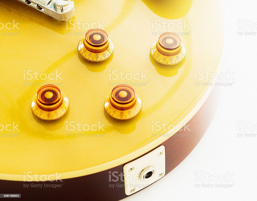 Electric guitar's control knobs and output jack in close up stock photo