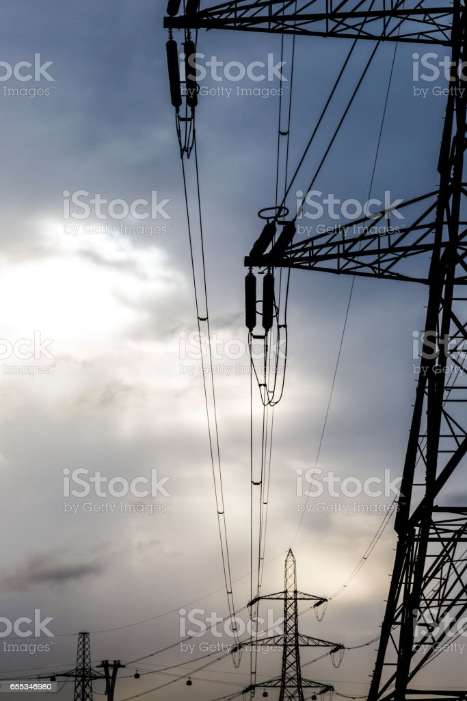 Electric high voltage polls in sunset light stock photo