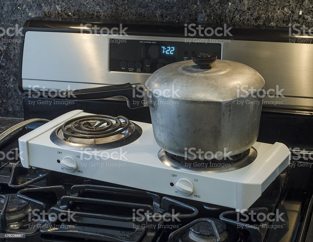 electric hot plate on top of gas range stock photo