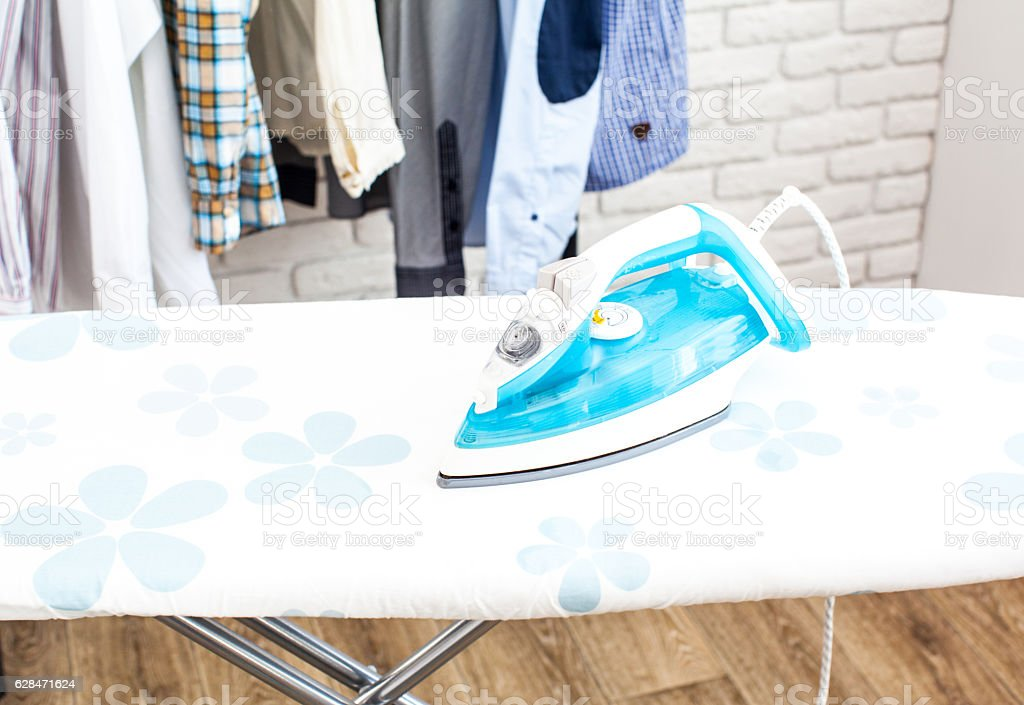 Electric iron and shirt, on cloth background stock photo