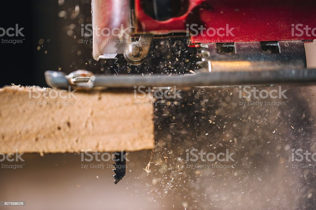 Electric jigsaw cutting a piece of wood. Close up royalty-free stock photo