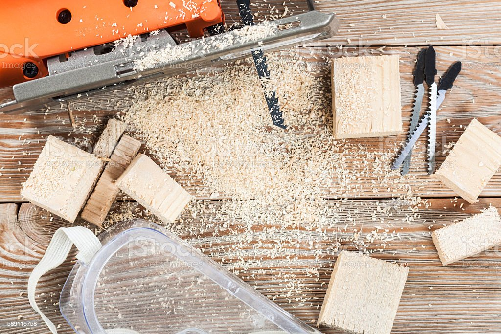 Electric jigsaw with many wooden bricks full of sawdust. stock photo