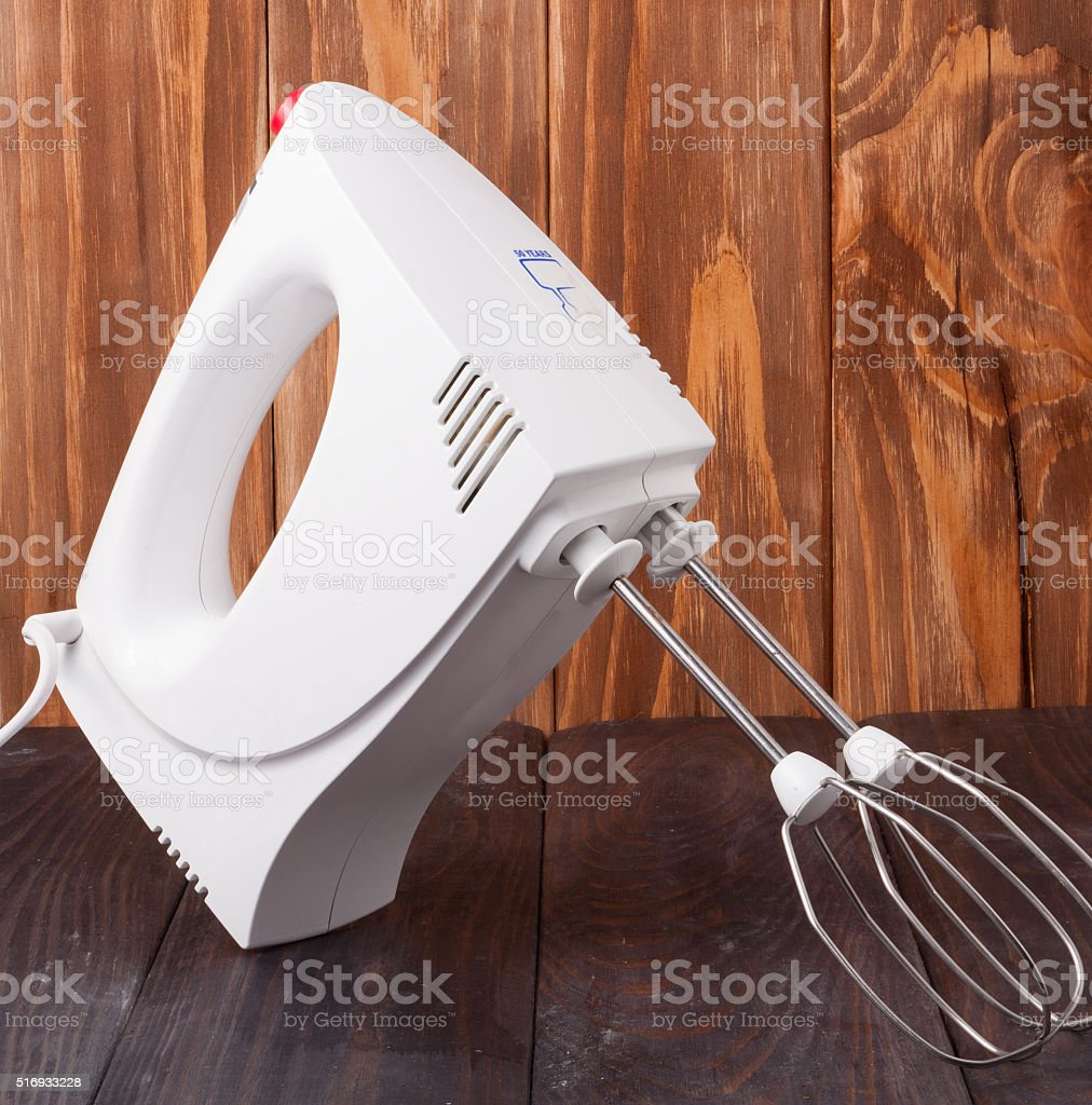 electric kitchenware beater with accessories on wooden background stock photo