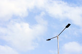 Electric lights and a pole against blue sky.