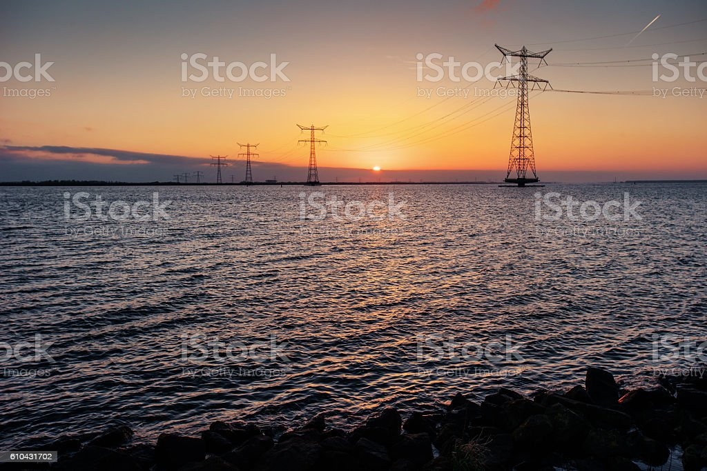 electric line above water during a fantastic sunset. stock photo