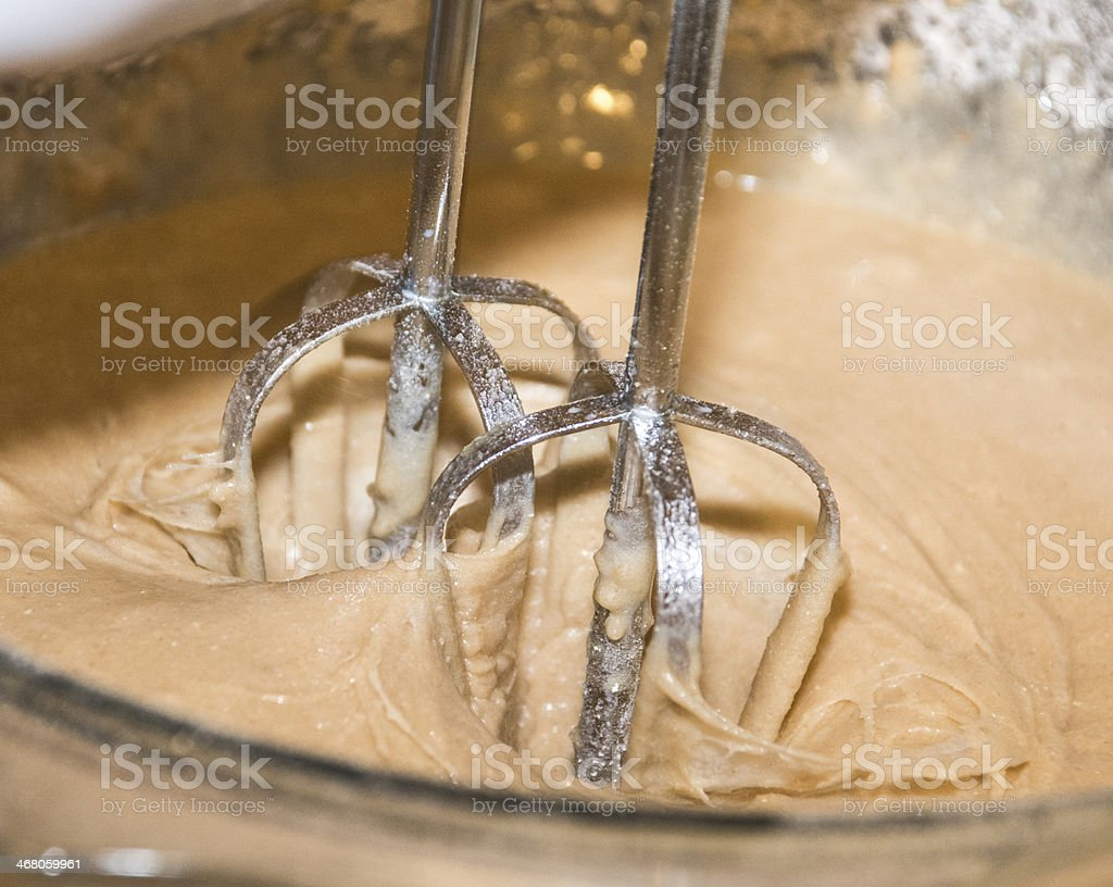 Electric mixer mixing cake mixture in a glass bowl stock photo