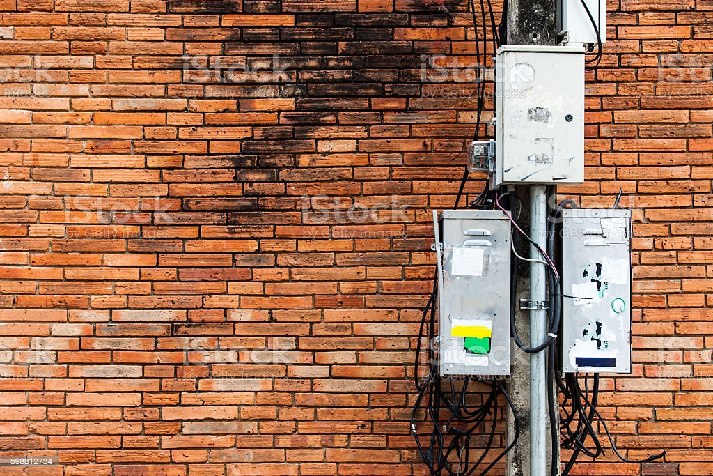 electric pole with dirty electrical control box and cable, brick stock photo