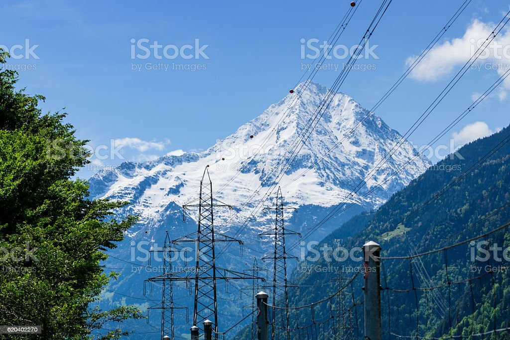 Electric poles in front of Swiss Alps stock photo