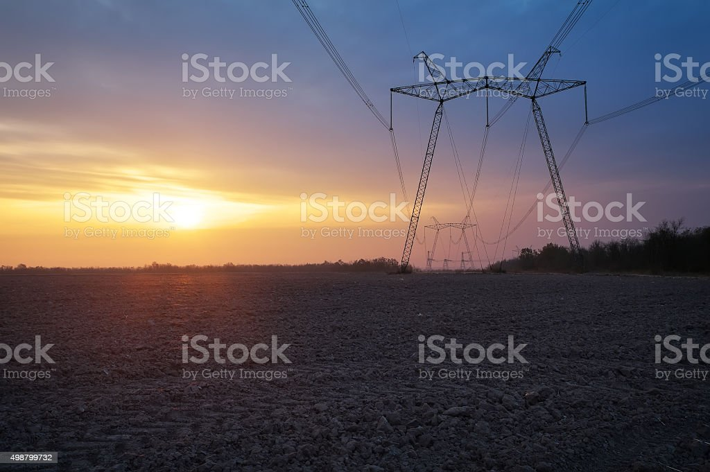 Electric power line at sunrise stock photo