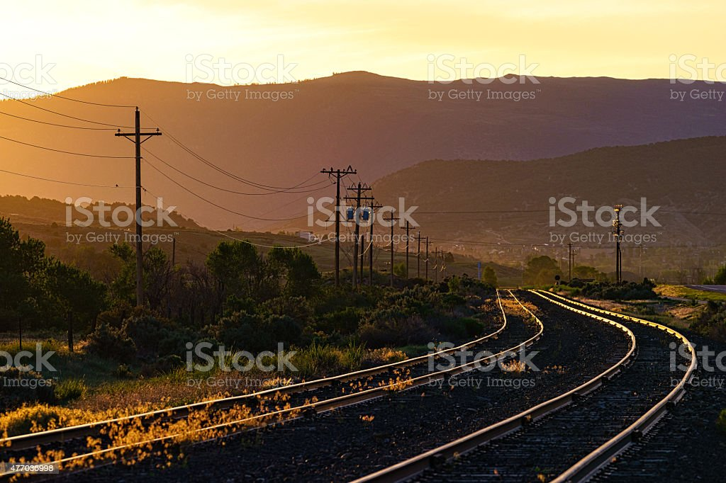 Electric Power Lines and Train Tracks at Sunrise stock photo