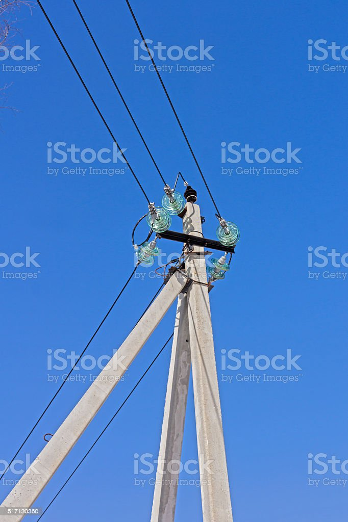 Electric power lines mounted on insulators and concrete pole stock photo