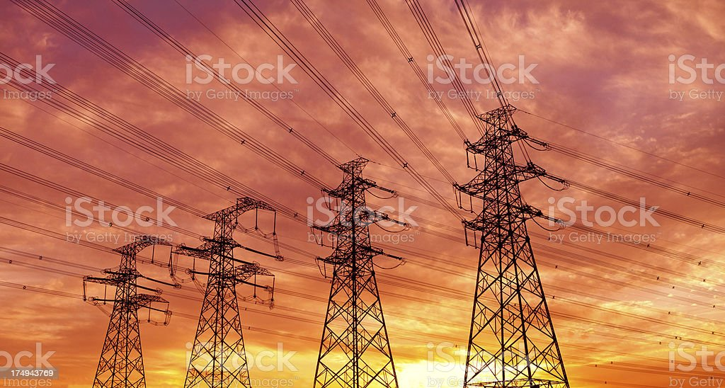 Electric power lines standing in front of the sunset stock photo