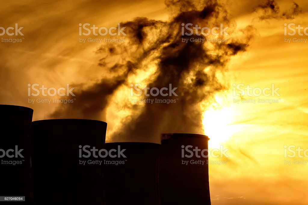 Electric power plant at dusk with orange sky stock photo