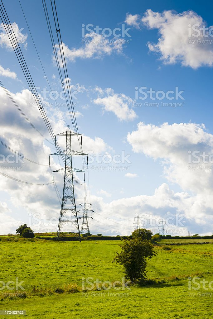 Electric Power Pylon Blue Sky Green Grass and White Clouds royalty-free stock photo