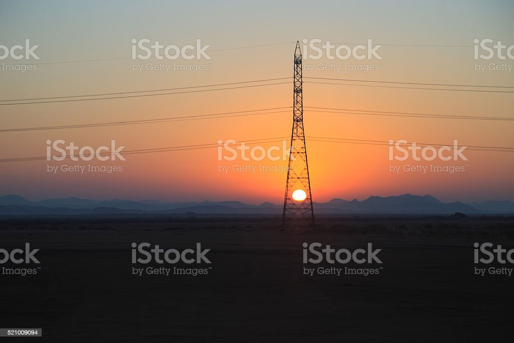 Electric power tower Under the setting sun stock photo