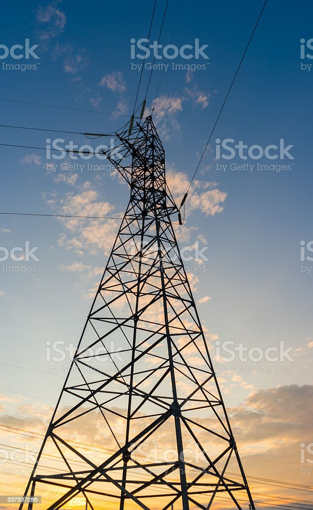 Electric power transmission against sky at sunset. stock photo