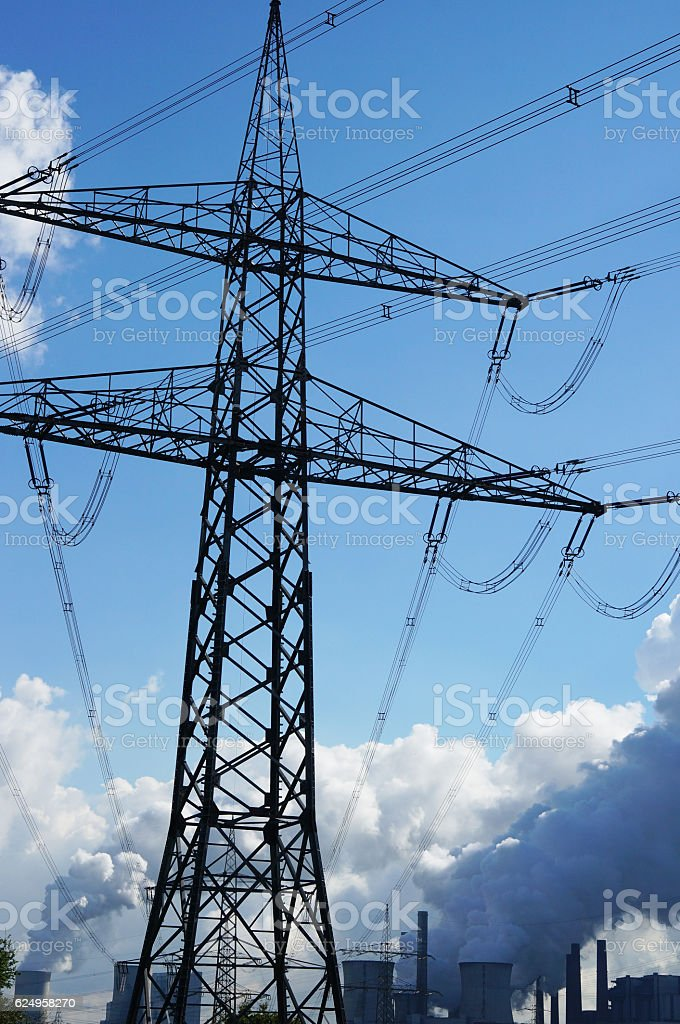 electric pylon in front of a power plant stock photo