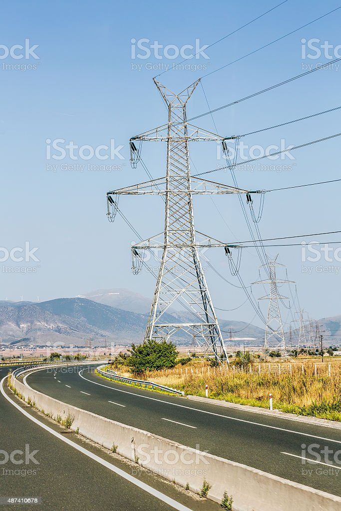 Electric Pylons, wind turbine and Highway stock photo