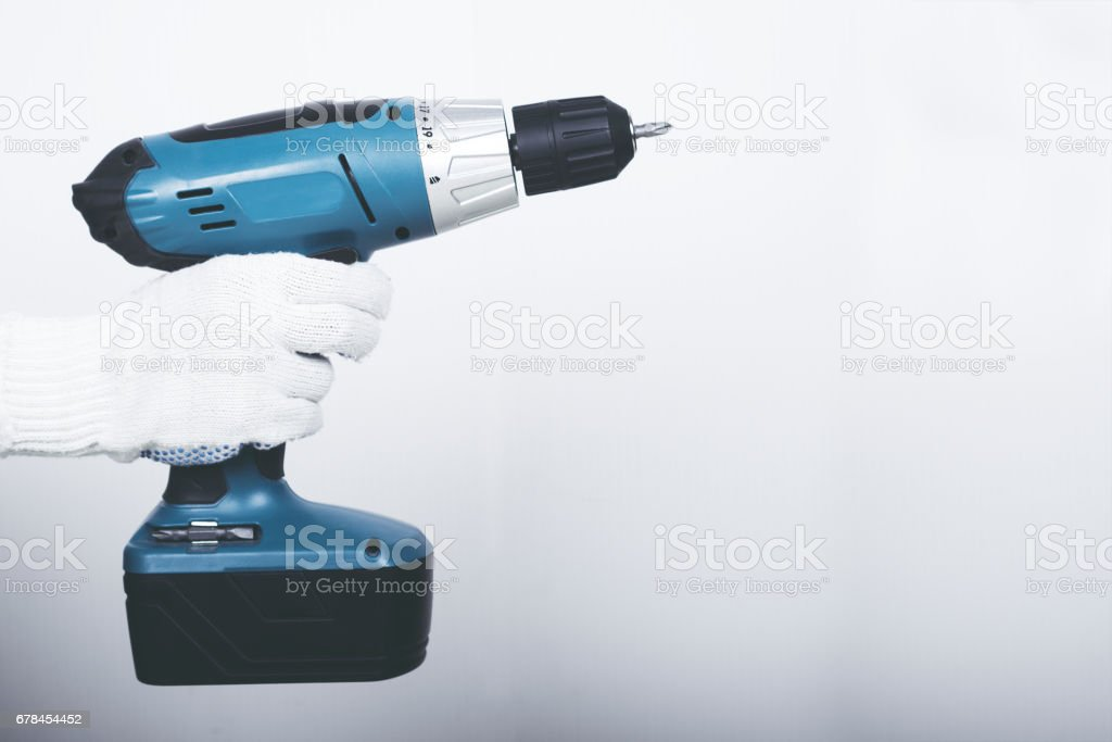 Electric screwdriver in hand at white desk background stock photo