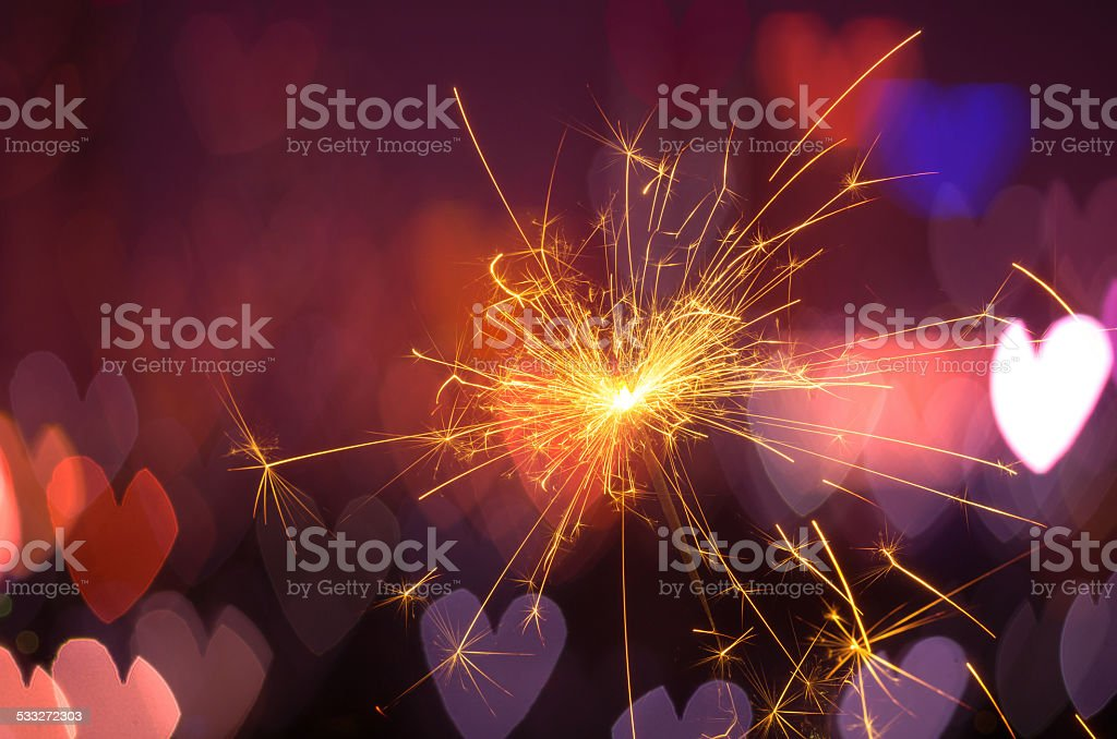 Electric sparklers with heart bokeh background stock photo