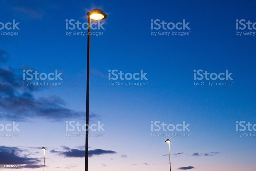 Electric street lamps at dusk stock photo