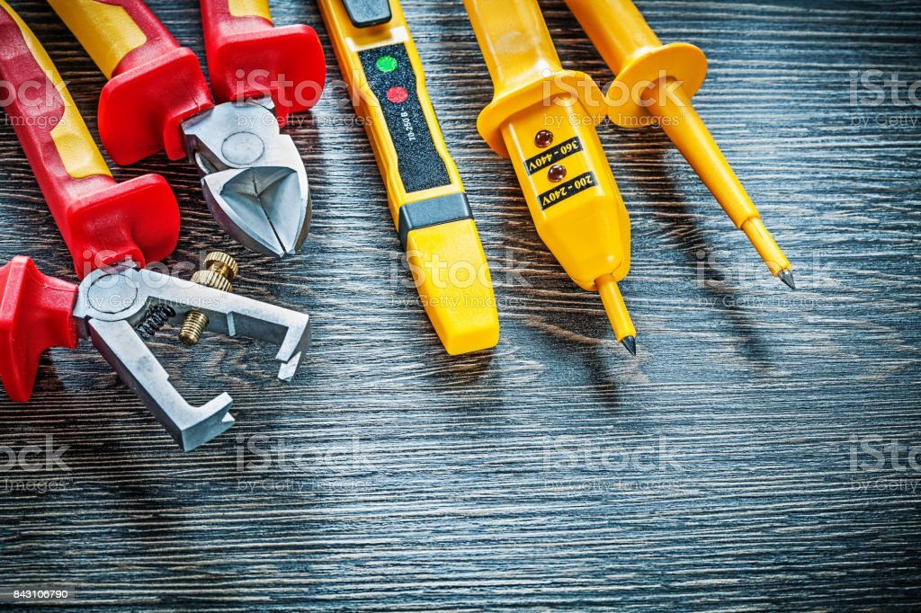 Electric tester nippers insulated strippers on wooden board stock photo
