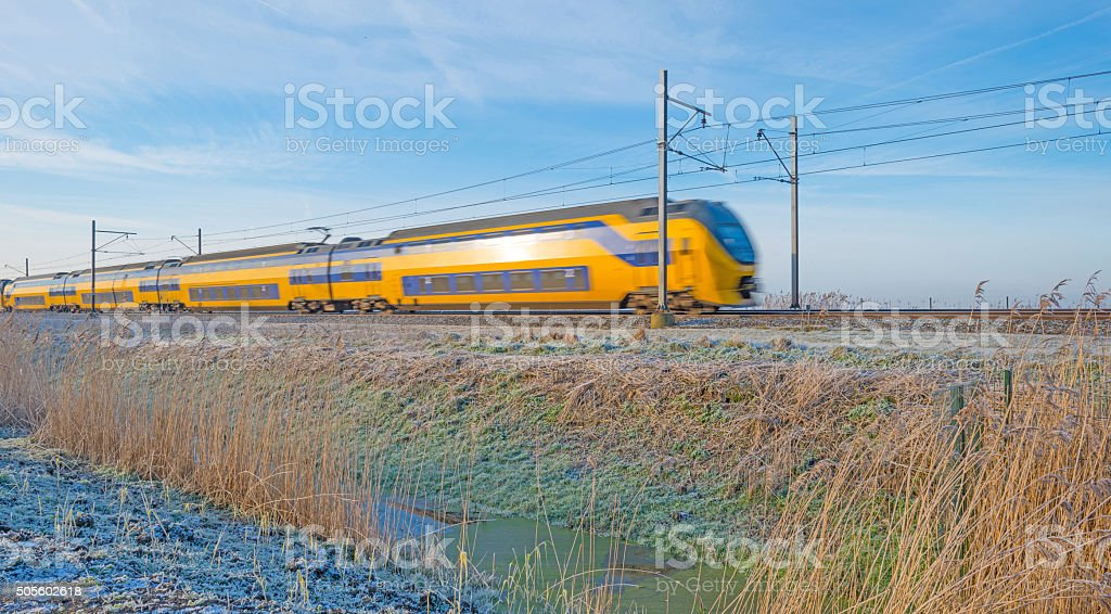 Electric train in a sunny frozen landscape stock photo