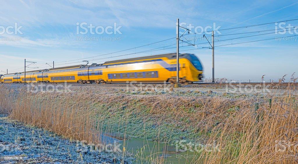 Electric train in a sunny frozen landscape stock photo