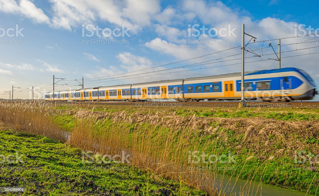 Electric train riding through nature in winter stock photo