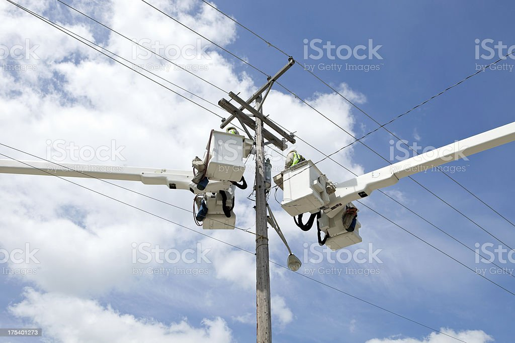 Electric Utility Workers in Truck Buckets near Pole stock photo