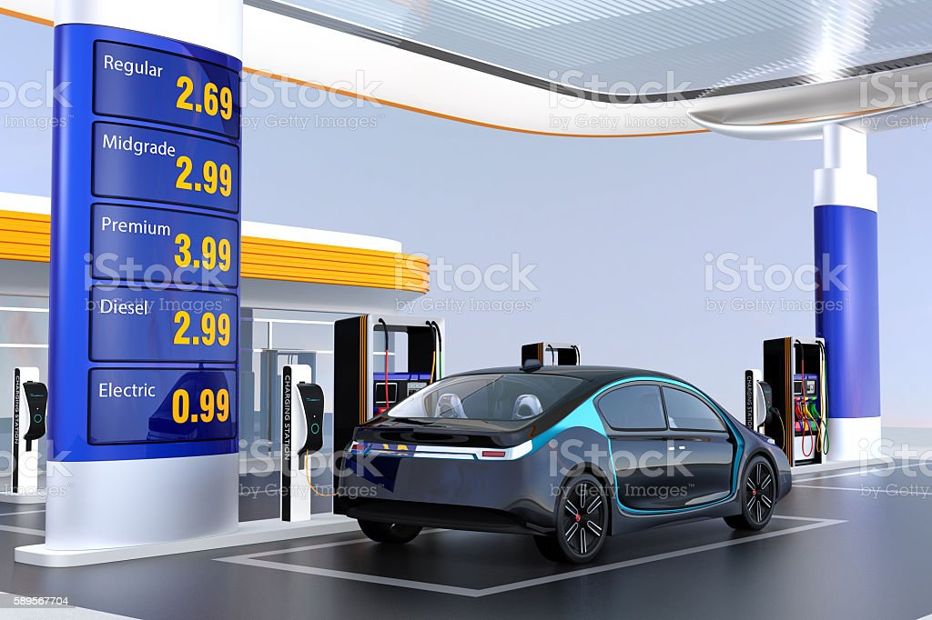 Electric vehicle charging at charging station stock photo